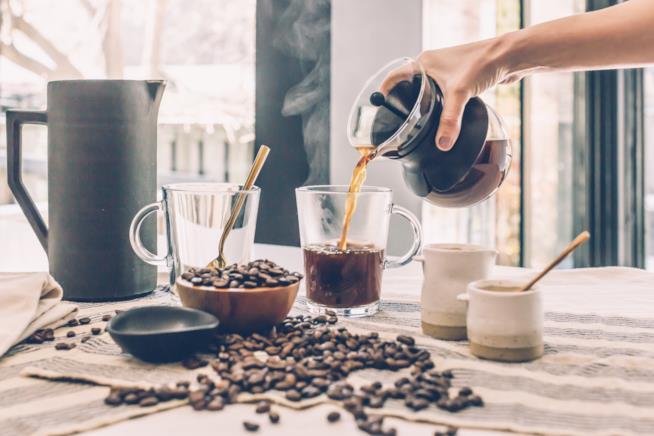 Un uomo versa del caffè americano in una tazza
