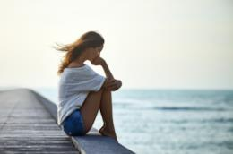 Ragazza sola seduta su un pontile