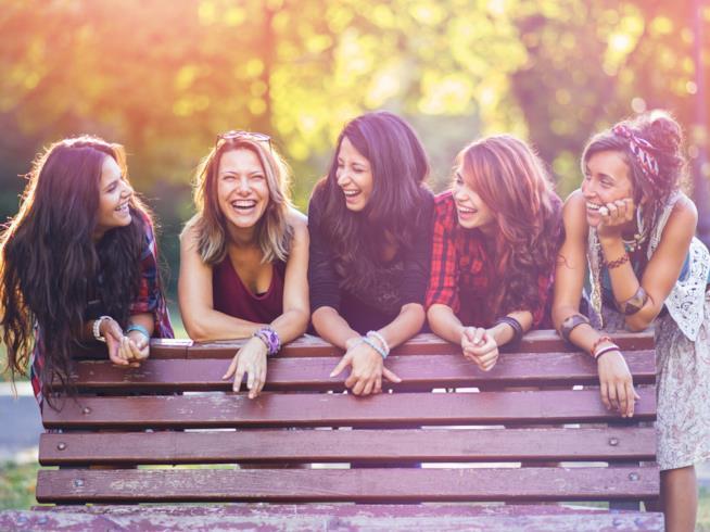 Gruppo di amiche sorride dietro una panchina