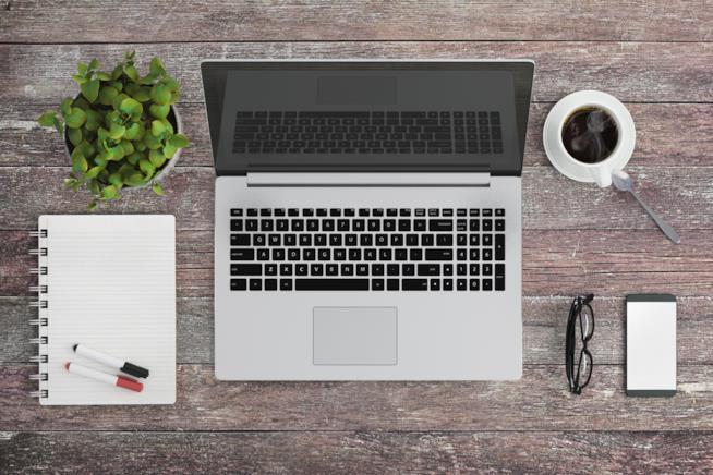 Una scrivania con computer, quaderno, penne, smartphone e occhiali