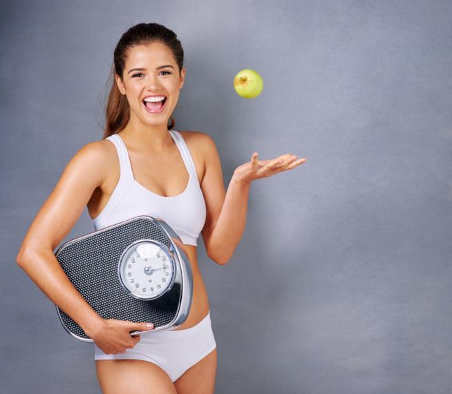 Una ragazza sorride tenendo una bilancia sottobraccio