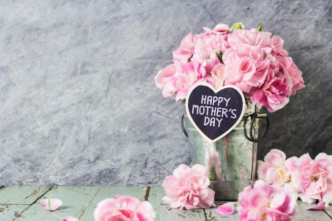 Vaso di fiori con biglietto d'auguri per la festa della mamma
