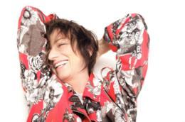 Primo piano della Nannini, sorridente, con una maglia con fantasia floreale, braccia dentro la nuca