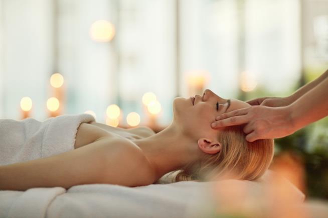 Una donna si rilassa facendo un massaggio alla testa