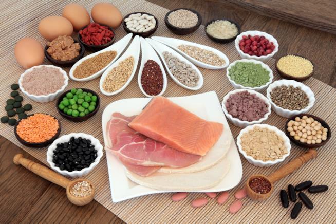 Diversi piattini e contenitori con legumi, pesce, carne bianca e uova