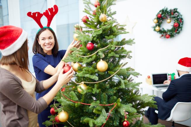 Due ragazze decorano l'albero di Natale in ufficio