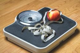 Bilancia con posati sopra un centimetro e una mela