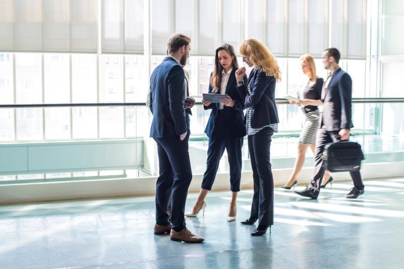 uomo e due donne conversano sul posto di lavoro