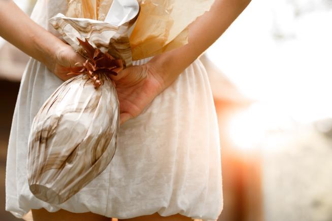Ragazza nasconde un uovo di cioccolato dietro la schiena