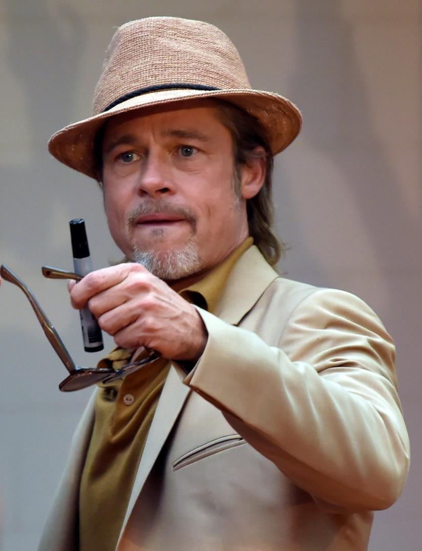 Mezzo busto di Brad Pitt, con un paio di occhiali da sole in mano