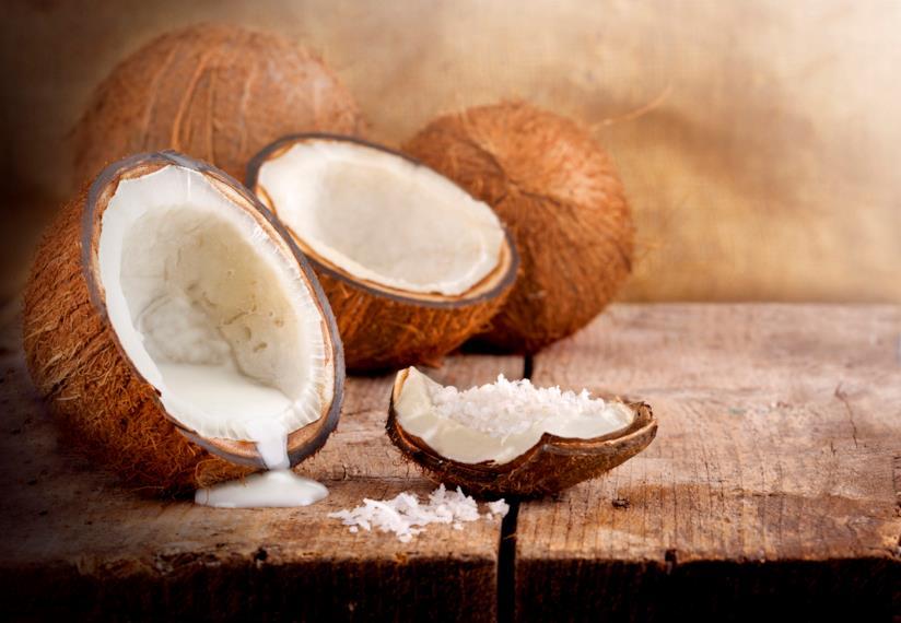 Noci di cocco con il latte di cocco che fuoriesce da esse