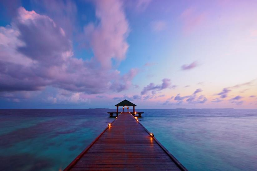 Un romantico tramonto in mezzo al mare delle Maldive
