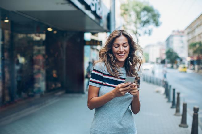 Una ragazza cammina per strada sorridendo mentre legge il display del telefono