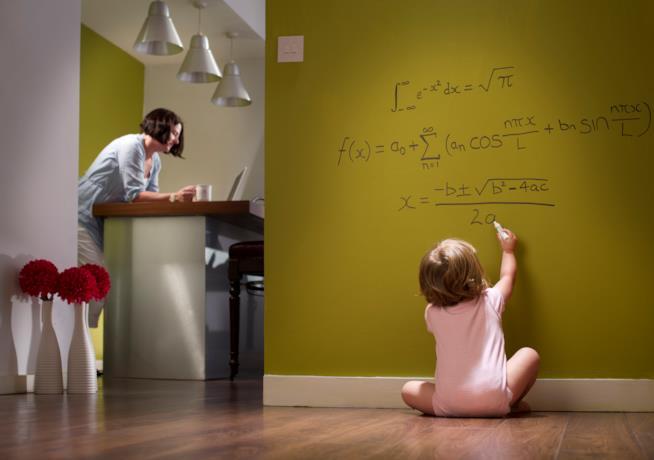 Una bambina che scrive sul muro formule matematiche.