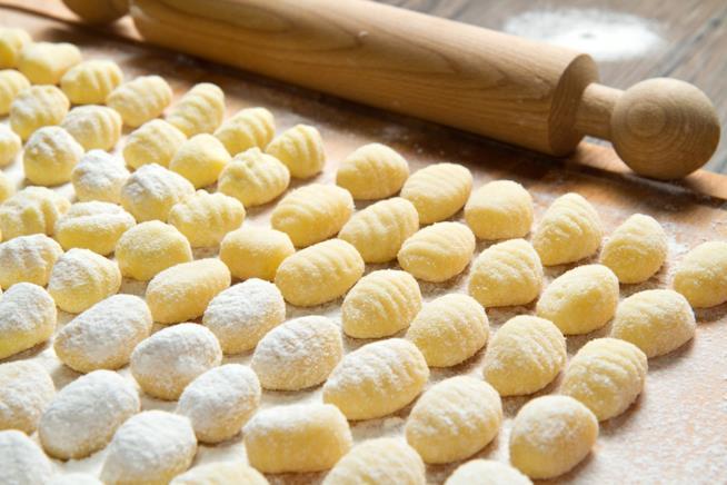 Tagliere di legno con gnocchi di patate cosparsi di farina e mattarello di legno in fondo