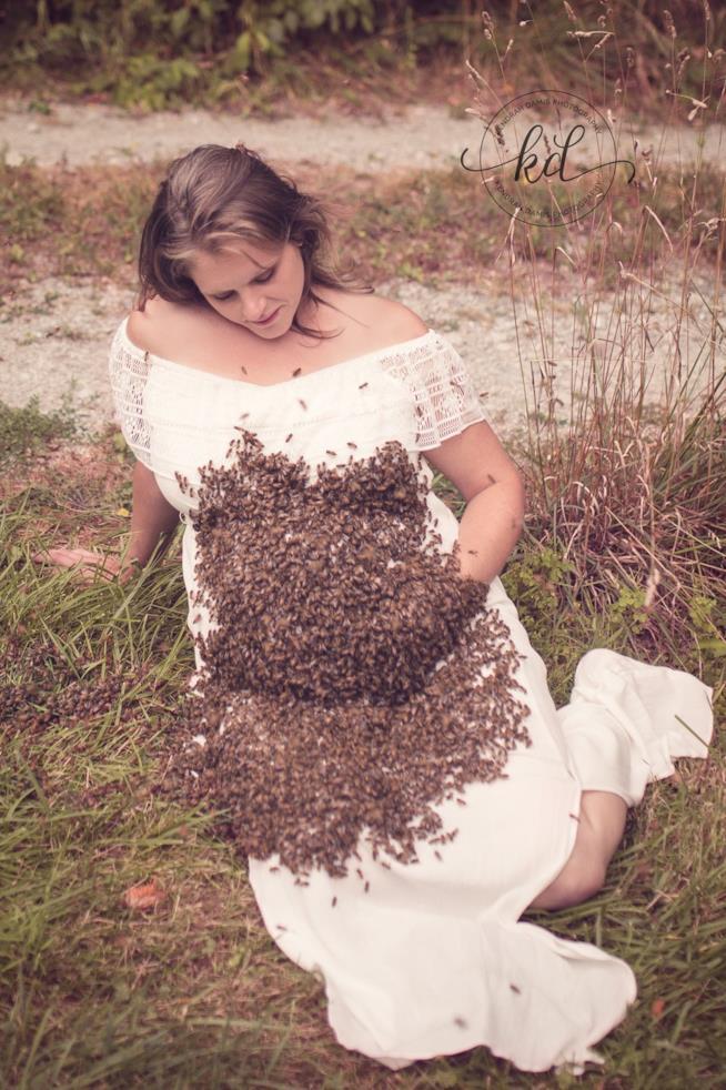 Una donna col pancione coperto di api