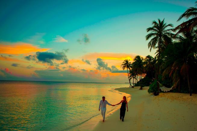 Coppia passeggia in spiaggia al tramonto
