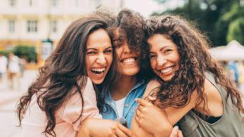 Tra ragazze si abbracciano sorridenti