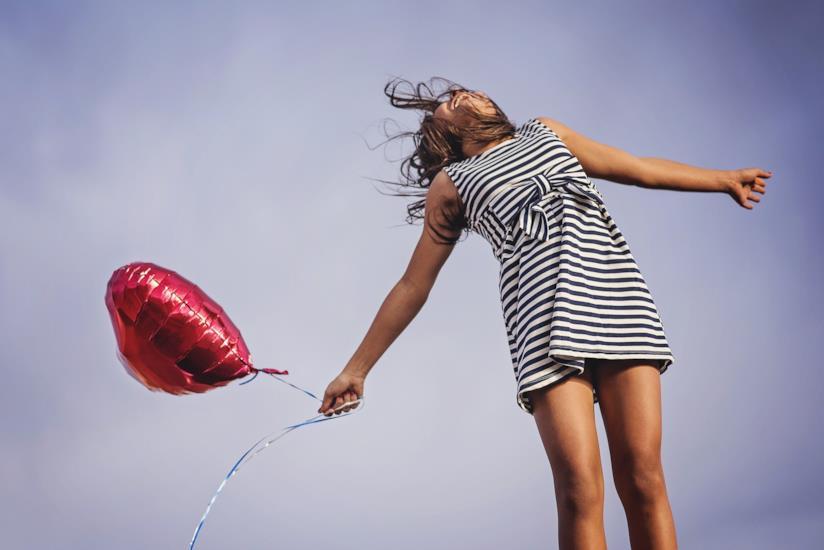Una ragazza con in mano un palloncino a forma di cuore