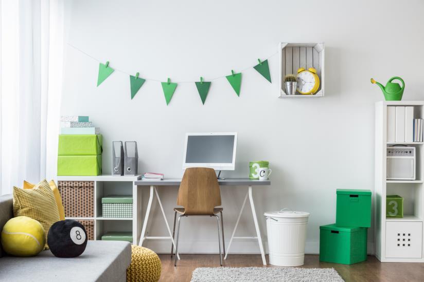 Cameretta per bambini e ragazzi arredata con mobili bianchi e accessori in verde