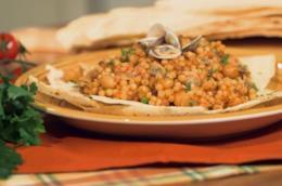 Primo piano di fregola sarda con vongole e ceci su piatto bianco