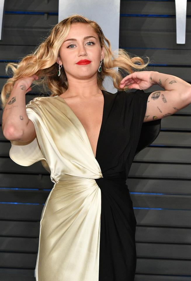 Miley Cyrus, in abito lungo, sistema i capelli mostrando i tattoos sulle braccia