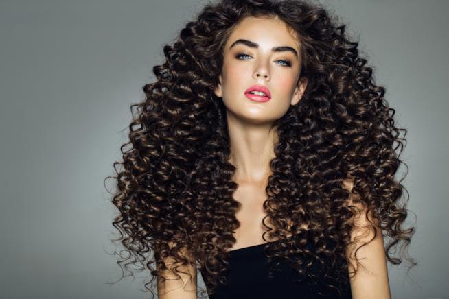 Giovane donna con bei capelli ricci