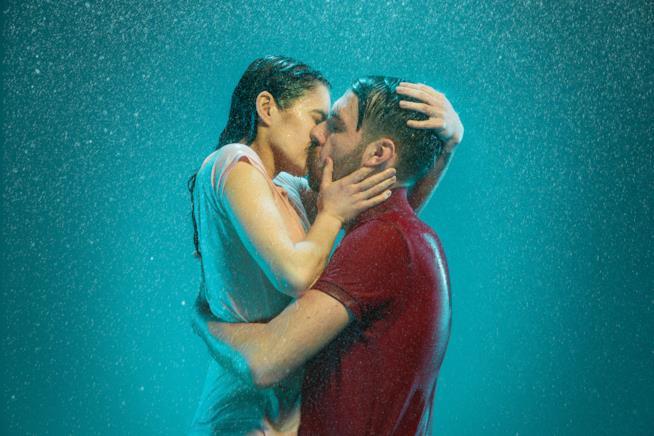 Un uomo e una donna si baciano sotto la pioggia