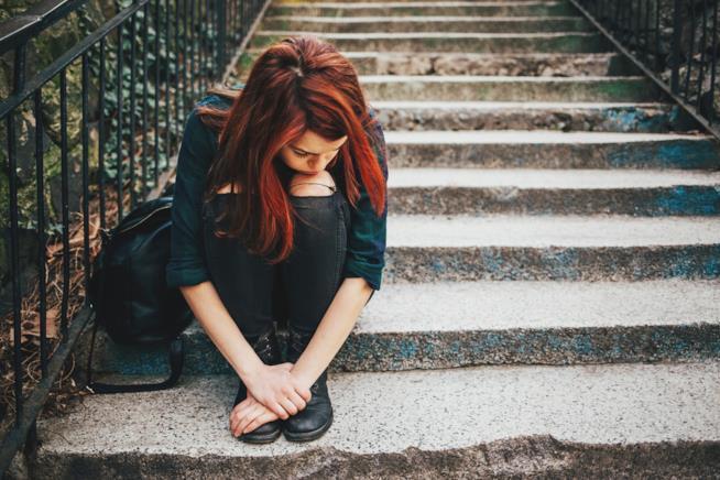 Ragazza seduta sulle scale con espressione triste
