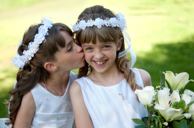 Due bambine vestite da Prima Comunione si abbracciano
