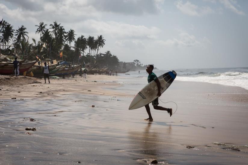 Un ragazzo con la tavola da surf in spiaggia