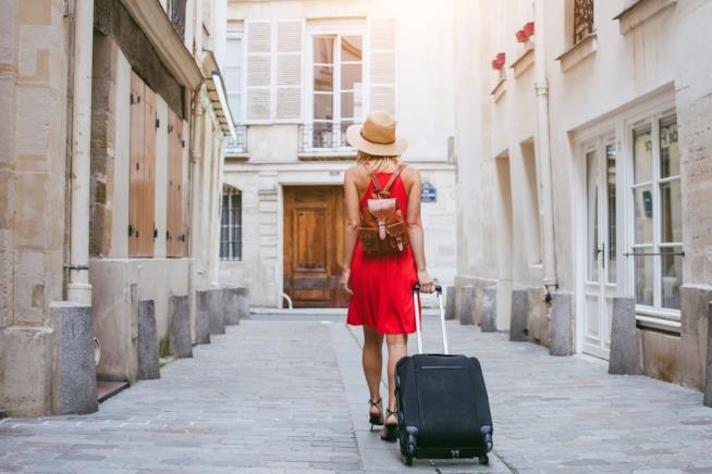 Una ragazza cammina lungo la strada con un trolley