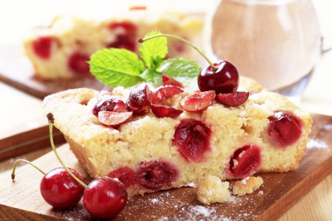 Quadrotto di torta allo yogurt e ciliegie con fogliolina di menta su tagliere di legno