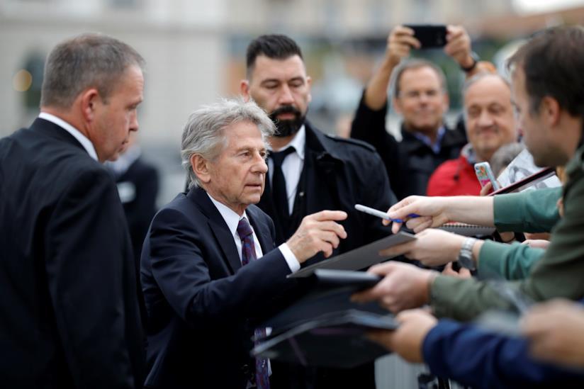 Roman Polanski, in piedi, firma autografi di fronte ai fan