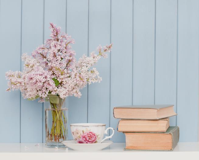 Scaffale con tazza di tè, alcuni libri e un mazzo di fiori freschi in vaso