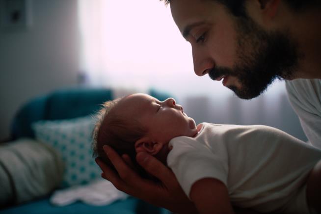 Un padre tiene in braccio la figlia neonata