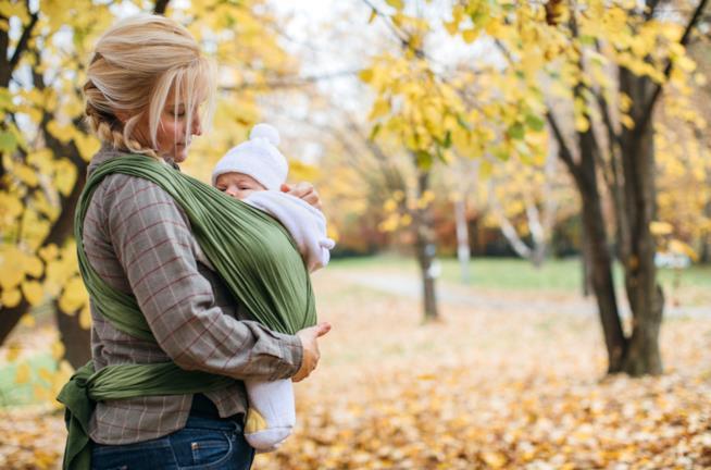 Mamma che porta il neonato nella fascia