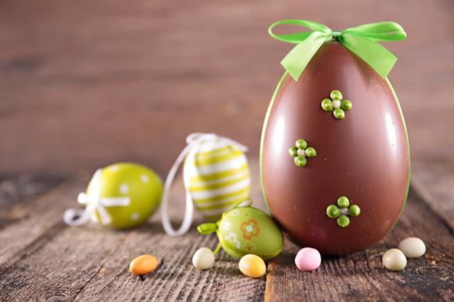 Uovo di cioccolato decorato con fiocco e fiorellini
