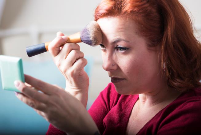 Donna applica fondotinta con pennello