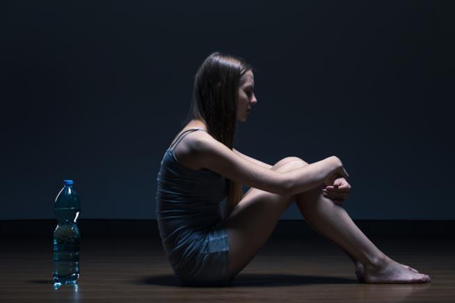 Ragazza seduta al buio