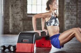 Atleta seduto su step da aerobica