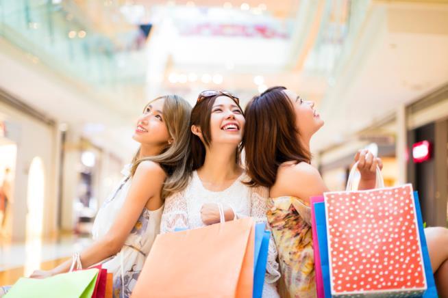 Tre ragazze sorridono felici mostrando le buste degli acquisti