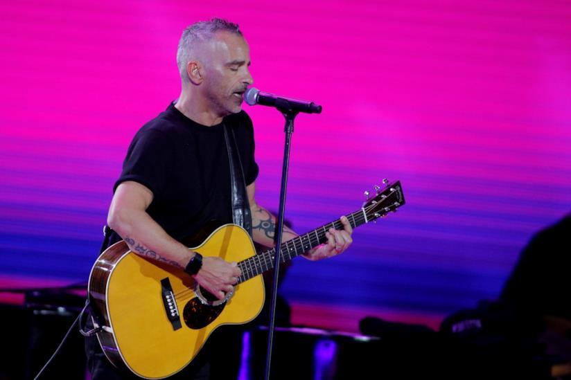 Eros Ramazzotti, in piedi, di fronte al microfono, canta e suona la chitarra acustica