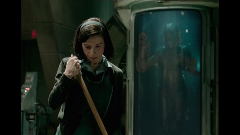 Eliza spazza il pavimento del laboratorio mentre la creatura la osserva