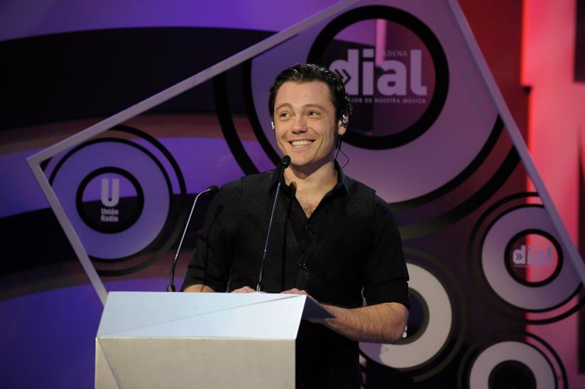 Tiziano Ferro, con una maglia nera, in piedi e di fronte a un microfono,