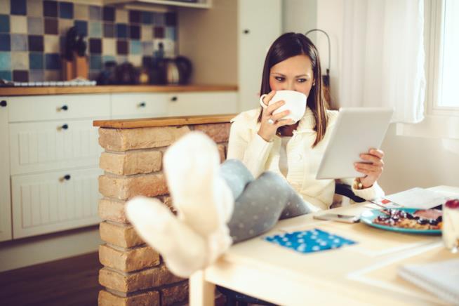 Una ragazza si rilassa bevendo un tè mentre legge seduta ad un tavolo