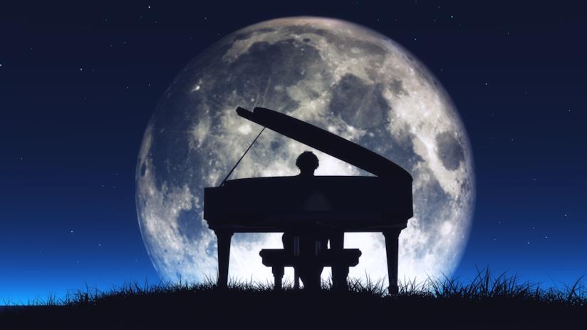 Pianista suona di notte in un prato sovrastato dalla luna