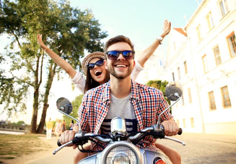 Un uomo e una donna vanno in giro in motorino