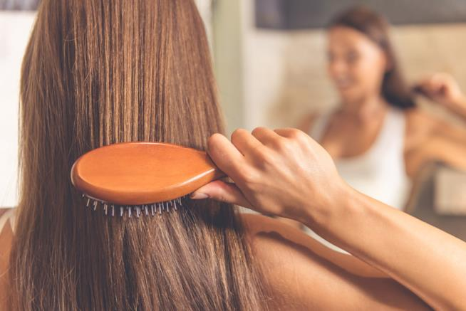 Ragazza si spazzola i capelli
