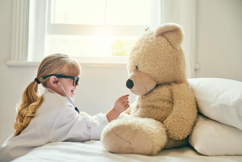Bambina vestita da medico visita un peluche